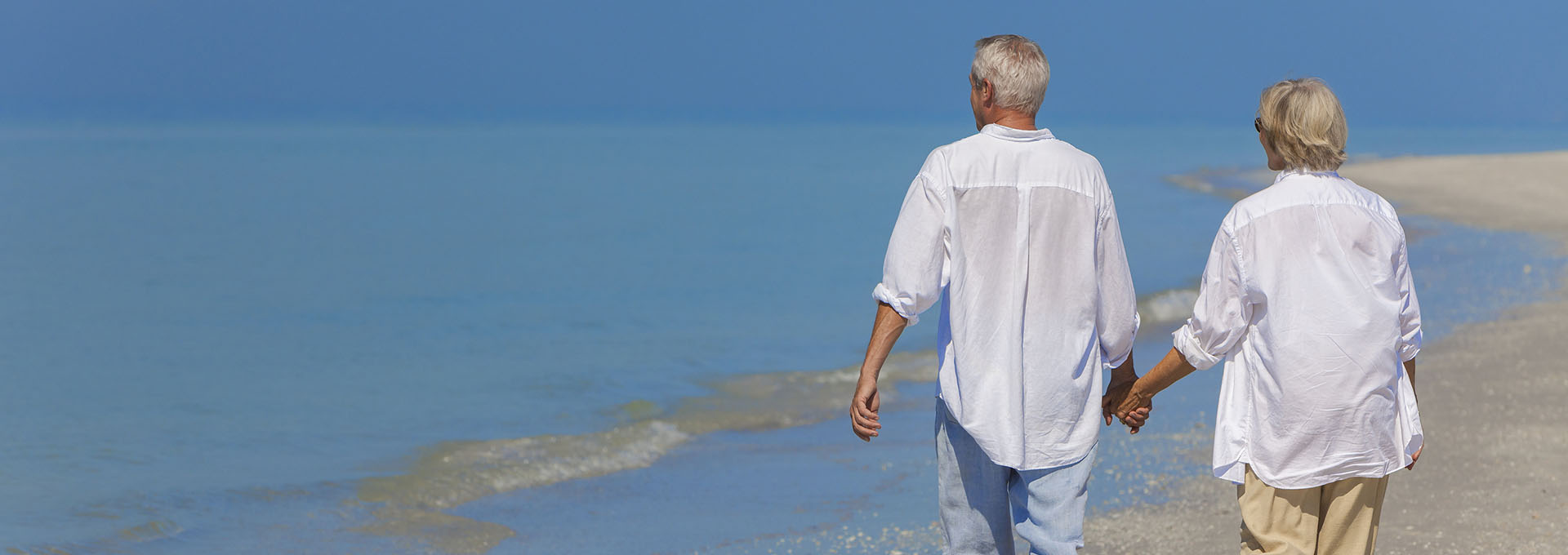 Senior man and woman couple holding hands walking on a deserted